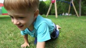 De jongen kruipt op alle fours op het gras stock footage