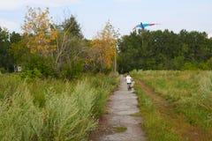 De jongen lanceert in de blauwe hemel een vlieger royalty-vrije stock foto's