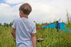 De jongen lanceert in de blauwe hemel een vlieger royalty-vrije stock afbeelding