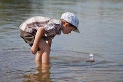 De jongen lanceert een kleine zeilboot Royalty-vrije Stock Afbeeldingen
