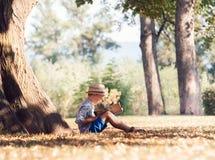 De jongen las een boek in boomschaduw in zonnige dag Stock Foto
