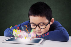 De jongen leert met tablet op bureau in klasse Royalty-vrije Stock Afbeeldingen