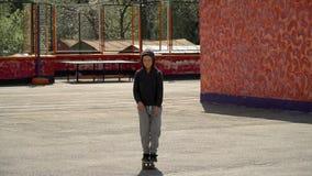 De jongen leert om een skateboard te berijden stock videobeelden