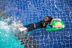 De jongen leert om in het zwembad te zwemmen Stock Foto's