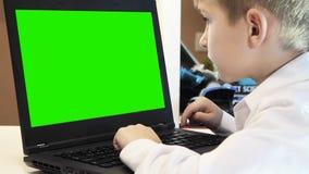 De jongen leert om op laptop in huis te typen stock video