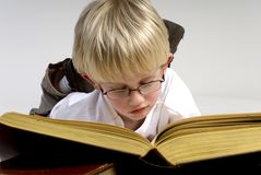 De jongen leest dikke boeken royalty-vrije stock afbeelding