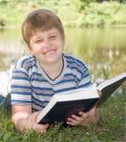 De jongen leest een boek Stock Foto's