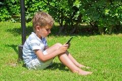 de jongen leest het e-boek Stock Afbeeldingen