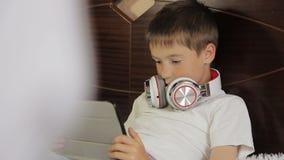 De jongen legt het luisteren aan muziek of heeft een e-lerende klasse gebruikend zijn tabletcomputer die aan een paar van wordt a stock video