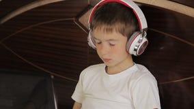 De jongen legt het luisteren aan muziek of heeft een e-lerende klasse gebruikend zijn tabletcomputer die aan een paar van wordt a stock footage