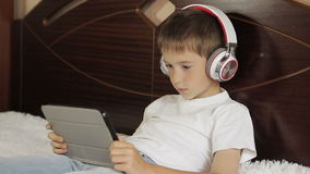 De jongen legt het luisteren aan muziek of heeft een e-lerende klasse gebruikend zijn tabletcomputer die aan een paar van wordt a stock videobeelden