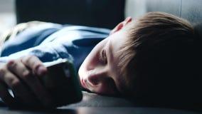 De jongen legt met zijn hoofd op de laag en kijkt droevige ogen met een smartphone Kinderen` s emoties ogen stock video
