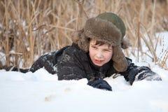 De jongen legt op sneeuw, de winter stock foto's