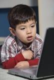 De jongen let op iets het interesseren. Stock Afbeeldingen