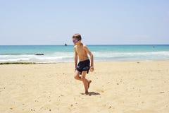 De jongen liep uit water Stock Foto's