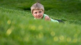 De jongen ligt in het groene gras op de helling stock fotografie