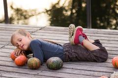 De jongen ligt met pompoenen Stock Foto