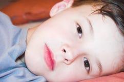 De jongen ligt op het bed Stock Foto