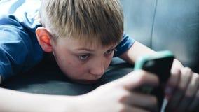 De jongen ligt op de laag en bekijkt het smartphonescherm Sluit omhoog stock videobeelden