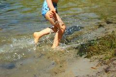 De jongen loopt in het water van meer Stock Foto