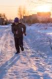 De jongen loopt op de weg in de winter bij zonsondergang stock afbeeldingen