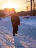 De jongen loopt op de weg in de winter bij zonsondergang royalty-vrije stock foto's