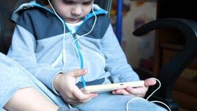De jongen luistert aan muziek door hoofdtelefoons In de ruimte van de kinderen geniet het kind van muziek stock footage