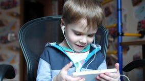 De jongen luistert aan muziek door hoofdtelefoons In de ruimte van de kinderen geniet het kind van muziek stock video