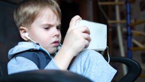 De jongen luistert aan muziek door hoofdtelefoons In de ruimte van de kinderen geniet het kind van muziek stock videobeelden