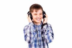 De jongen luistert aan muziek in hoofdtelefoons en het is zeer pret in Th Royalty-vrije Stock Foto
