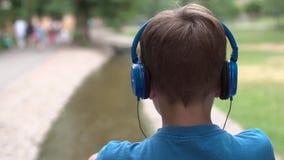 De jongen luistert aan muziek op hoofdtelefoons stock footage