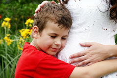 De jongen luistert aan zijn zwanger mamma Stock Afbeeldingen