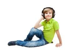 De jongen luistert muziek, op wit wordt geïsoleerd dat Stock Foto