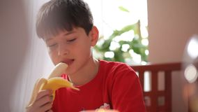 De jongen maakt banaan bij de lijst schoon stock footage