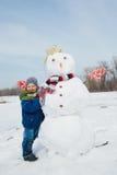 De jongen maakt een sneeuwman Stock Foto's