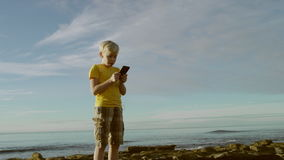 De jongen maakt een videovertaling voor de rest van zijn familie op een strand stock videobeelden