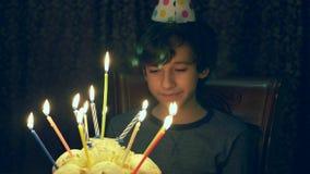 De jongen maakt een wens en bekijkt de kaarsen op de cake in de donkere ruimte slow-motion 4k, stock videobeelden