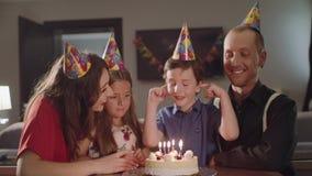 De jongen maakt een wens en blaast kaarsen op een verjaardagscake stock video