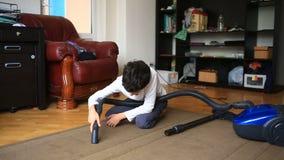 De jongen maakt het tapijt in de ruimte met een stofzuiger schoon stock videobeelden