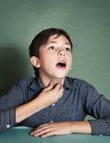 De jongen maakt het zingen oefeningen op blauwe achtergrond Stock Foto's