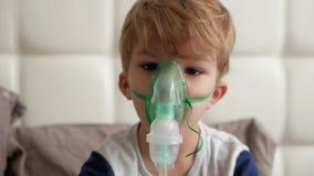 De jongen maakt inhalatie de geneeskunde stock footage