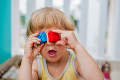 De jongen maakt ogen van kleurrijke kinderen` s blokken Leuk weinig jong geitjejongen die met glazen met binnen veel kleurrijke p Stock Afbeeldingen