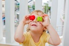 De jongen maakt ogen van kleurrijke kinderen` s blokken Leuk weinig jong geitjejongen die met glazen met binnen veel kleurrijke p stock fotografie