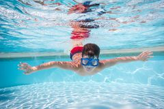 De jongen in masker duikt in zwembad stock foto's
