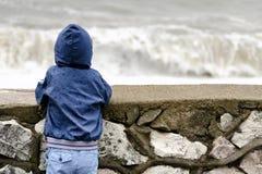 De jongen in matroos met kap bevindt zich met zijn rug tegen de pijler tegen de achtergrond van overzeese golven Royalty-vrije Stock Afbeeldingen