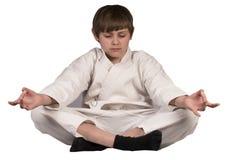De jongen mediteert zitting in Kim Stock Foto