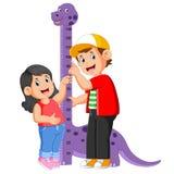 De jongen meet zijn zuster op de hoogte van de dinosaurusmaatregel stock illustratie
