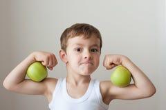 De jongen met appelen toont bicepsen royalty-vrije stock afbeelding