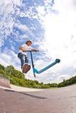 De jongen met autoped gaat in de lucht Stock Afbeelding