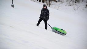 De jongen met buizenstelsel beklimt helling in de winter stock footage